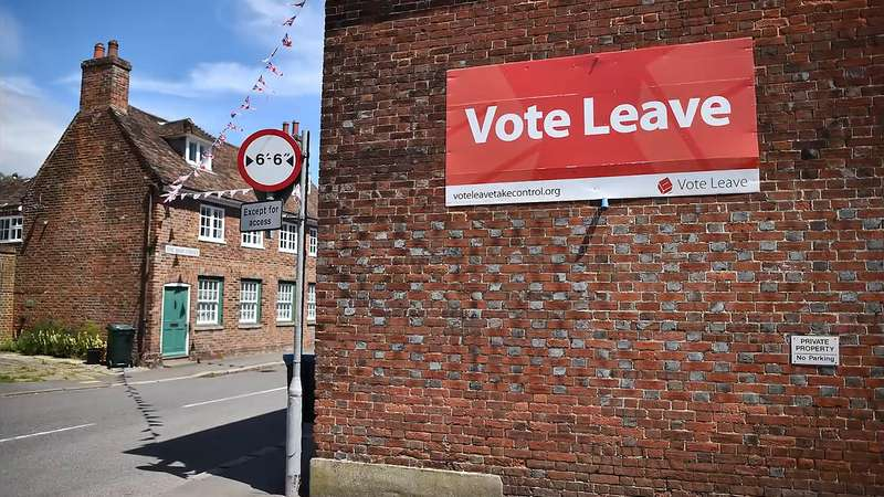 """A sign aside a brick building, indicating """"Vote Leave."""""""